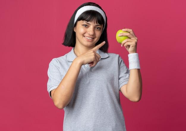 Молодая фитнес-девушка с повязкой на голову держит зеленое яблоко, указывая указательным пальцем на яблоко, весело улыбаясь, стоя на розовом фоне