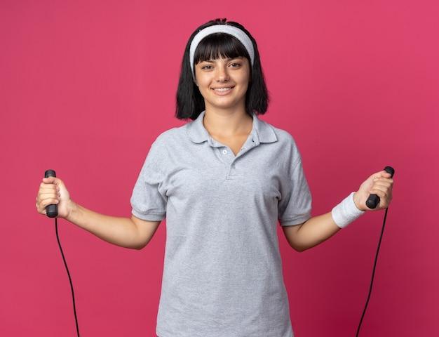줄넘기를 들고 머리띠를 한 젊은 피트니스 소녀는 분홍색 배경 위에 서서 웃고 있는 카메라를 보며 행복하고 쾌활합니다.