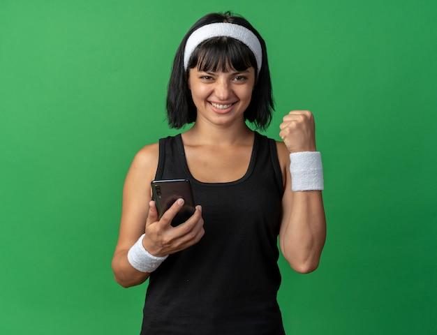 스마트 폰 떨림 주먹을 들고 머리띠를 착용하는 젊은 피트니스 소녀 행복하고 카메라를보고 흥분