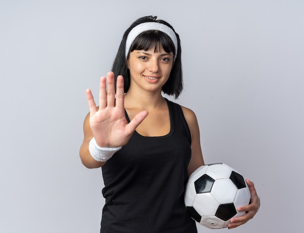 Young fitness girl wearing headband holding soccer ball looking at camera smiling doing stop gesture with hand standing over white