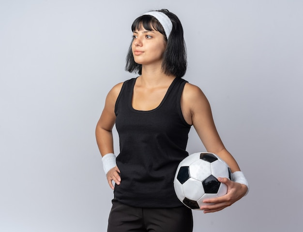 白の上に立っている深刻な顔のボールで脇を見てサッカーを保持しているヘッドバンドを身に着けている若いフィットネスの女の子