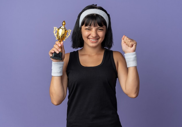 Young fitness girl wearing headband holding trophy happy and excited raising fist rejoicing her success standing over blue