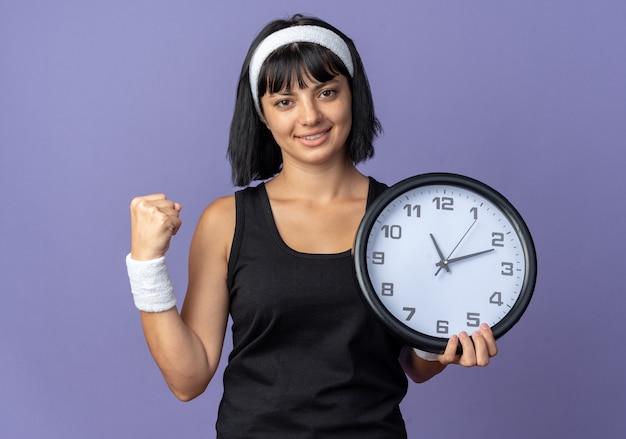 Giovane ragazza di forma fisica che indossa la fascia che tiene l'orologio da parete che guarda l'obbiettivo felice e fiducioso che stringe il pugno in piedi su sfondo blu