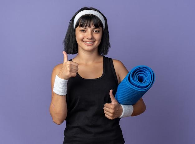 요가 매트를 들고 머리띠를 한 젊은 피트니스 소녀가 파란 배경 위에 엄지손가락을 들고 즐겁게 웃고 있는 카메라를 바라보고 있습니다.