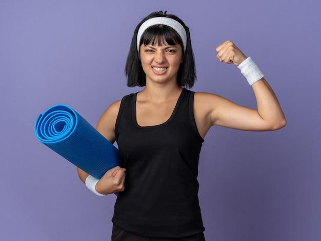 요가 매트를 들고 머리띠를 한 젊은 피트니스 소녀가 파란 배경 위에 긴장되고 자신감 있게 서 있습니다.