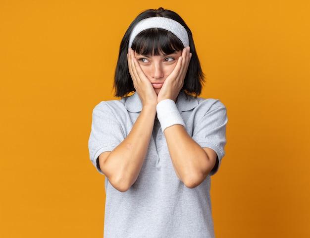 오렌지 위에 서있는 그녀의 뺨에 손으로 혼란스럽고 걱정하는 머리띠를 착용 한 젊은 피트니스 소녀