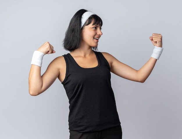 Giovane ragazza fitness che indossa la fascia che guarda da parte felice e allegra alzando i pugni in piedi su bianco