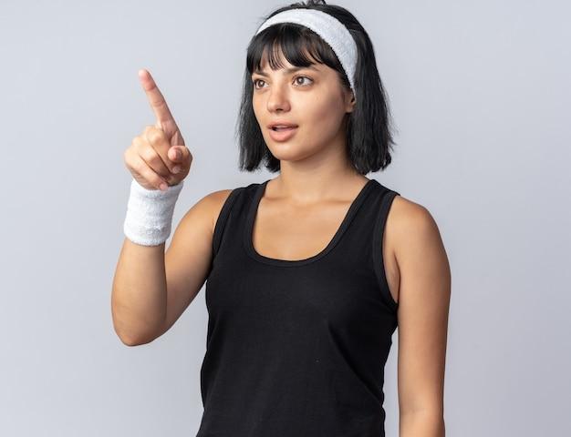 머리띠를 한 젊은 피트니스 소녀가 흰색 배경 위에 서 있는 무언가를 검지 손가락으로 가리키며 흥미롭게 바라보고 있습니다.