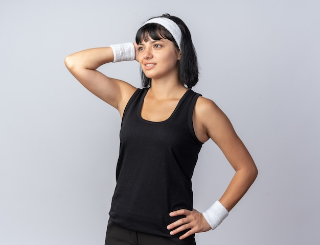 Молодая фитнес-девушка в повязке на голову, глядя в сторону, улыбаясь, держа руку на голове, думая о позитивном положении над белой