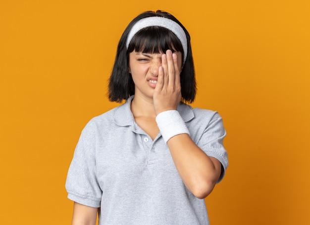 카메라를보고 머리띠를 착용하는 젊은 피트니스 소녀 오렌지 위에 서있는 손으로 눈을 덮고 혼란스럽고 불쾌한