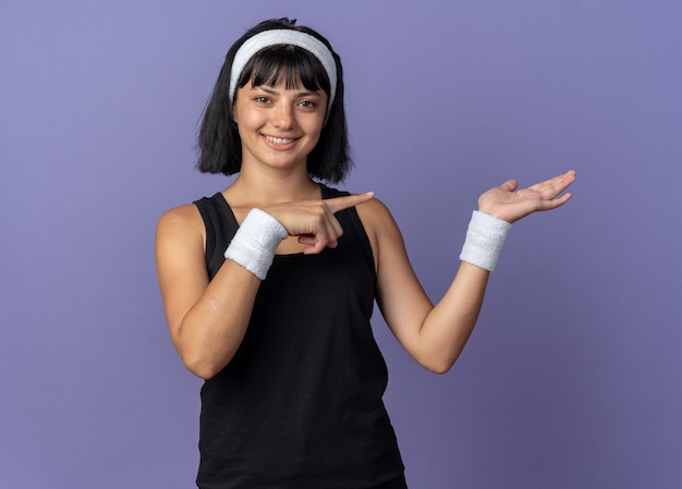 머리띠를 하고 있는 젊은 피트니스 소녀는 파란색 배경 위에 자신감 있게 서서 웃고 있는 쪽을 검지 손가락으로 가리키는 손으로 복사 공간을 제시하는 카메라를 보고 있습니다.