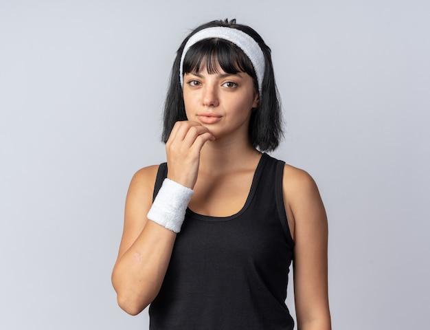 흰색 배경 위에 서 있는 의아해 카메라를 바라보는 머리띠를 한 젊은 피트니스 소녀