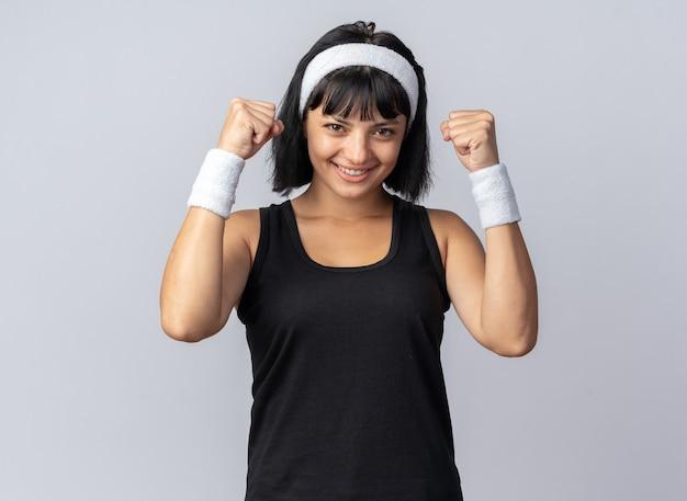 흰색 위에 서있는 유쾌하게 행복하고 흥분 제기 주먹 미소를 카메라를보고 머리띠를 착용하는 젊은 피트니스 소녀