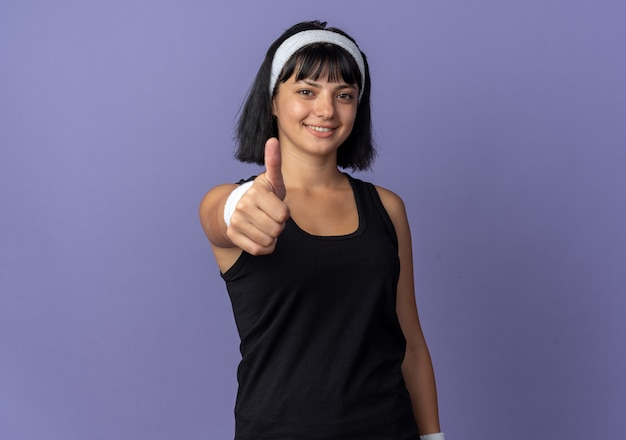 자신감을 보여주는 엄지 손가락을 웃는 카메라를보고 머리띠를 착용하는 젊은 피트니스 소녀