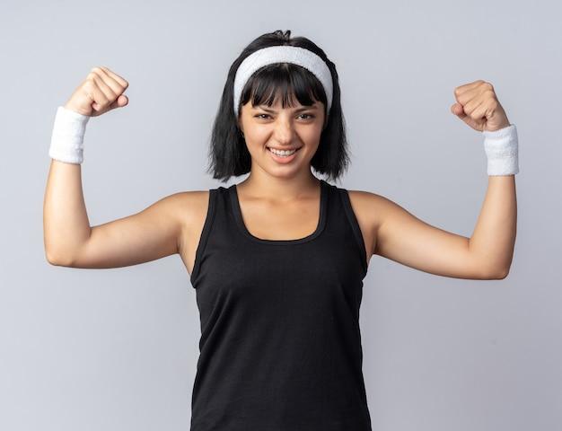 머리띠를 하고 카메라를 바라보는 젊은 피트니스 소녀는 흰색 배경 위에 서 있는 긴장되고 자신감 있는 주먹을 들고 있다
