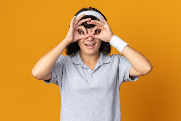 머리띠를 하고 손가락으로 카메라를 바라보는 젊은 피트니스 소녀는 주황색 배경 위에 즐겁게 서서 쌍안 제스처를 하고 있다