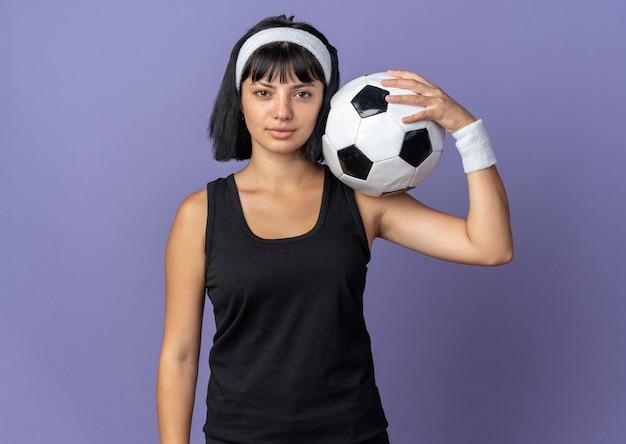 심각한 자신감 표정으로 카메라를보고 머리띠를 착용하는 젊은 피트니스 소녀