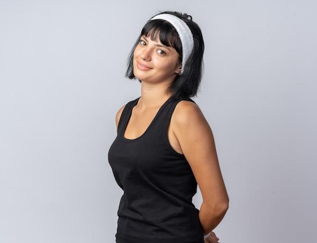 흰색 배경 위에 서 있는 얼굴에 수줍은 미소를 띠고 카메라를 바라보는 머리띠를 한 젊은 피트니스 소녀