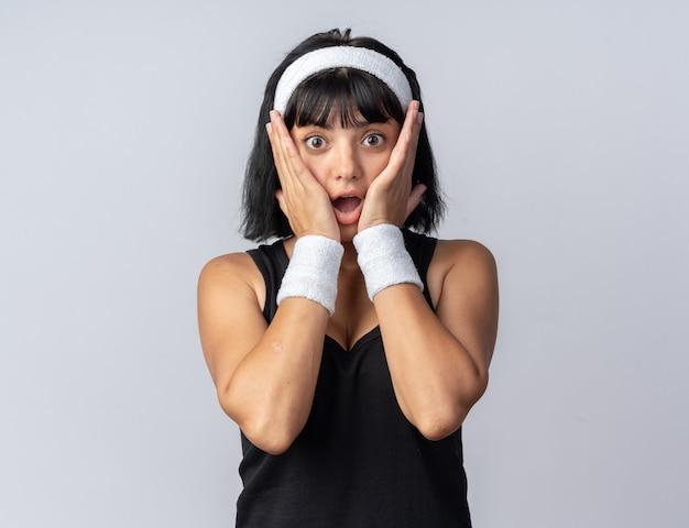 Giovane ragazza di forma fisica che indossa la fascia guardando la telecamera stupita e sorpresa in piedi sopra il bianco