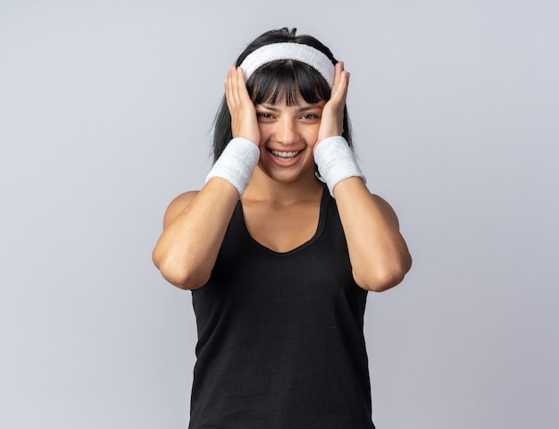 Young fitness girl wearing headband looking at camera hapy and cheerful smiling standing over white