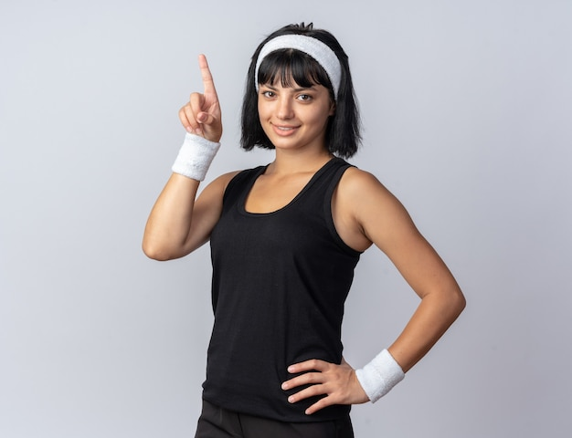 Young fitness girl wearing headband looking at camera smiling confident pointing with index finger up standing over white