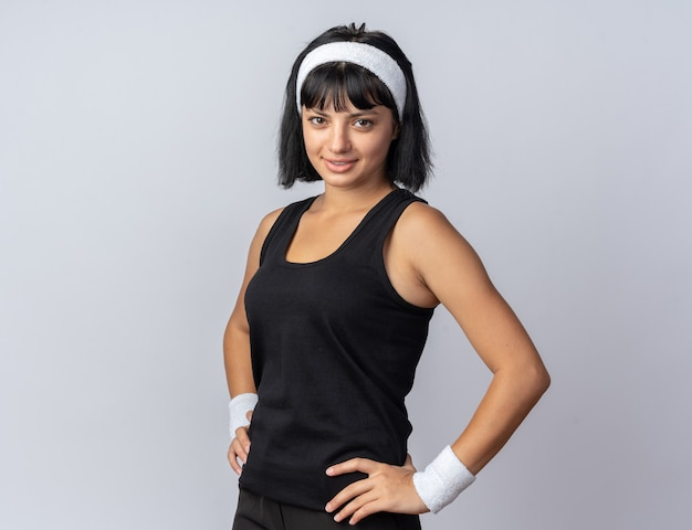 Young fitness girl wearing headband looking at camera smiling confident standing over white