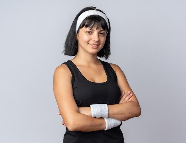 Giovane ragazza di forma fisica che indossa la fascia che guarda l'obbiettivo sorridente fiducioso con le braccia incrociate in piedi su sfondo bianco