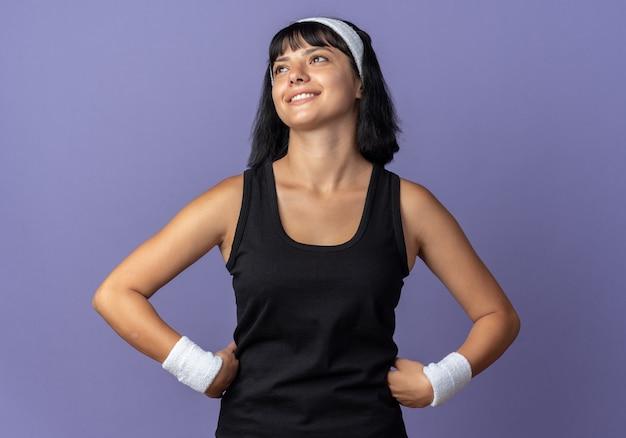 머리띠를 한 젊은 피트니스 소녀가 파란 배경 위에 유쾌하게 행복하고 긍정적인 미소를 짓고 있습니다.