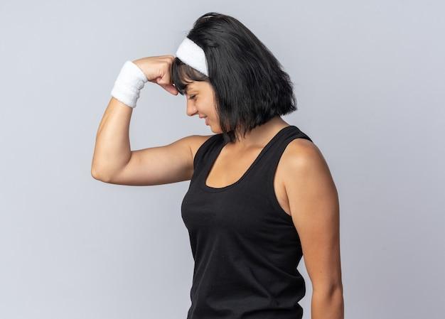 Giovane ragazza di forma fisica che indossa la fascia alzando il pugno che sembra fiducioso sorridente fiducioso in piedi su bianco