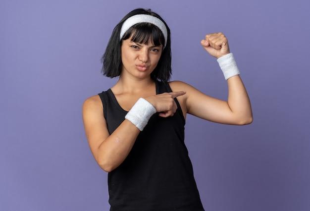 머리띠를 한 젊은 피트니스 소녀가 검지 손가락으로 가리키는 팔뚝을 보여주는 주먹을 들고 파란색 배경 위에 자신감 있게 서 있는 것처럼 보입니다.