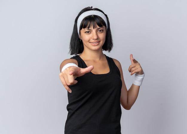 흰색 배경 위에 서 있는 카메라를 검지 손가락으로 가리키며 즐겁게 웃고 있는 머리띠를 한 젊은 피트니스 소녀