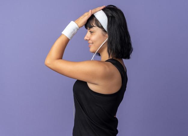 파란색 위에 자신감을 찾고 옆으로 서있는 머리띠를 착용하는 젊은 피트니스 소녀