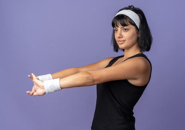 Giovane ragazza di forma fisica che indossa la fascia che allunga le sue mani pronte per allenarsi guardando fiducioso in piedi sopra il blu