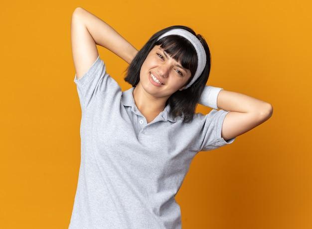 혼란스럽고 불쾌한 찾고 자신을 스트레칭하는 머리띠를 착용하는 젊은 피트니스 소녀