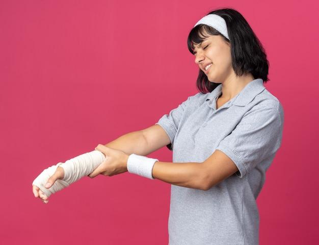 머리띠를 하고 붕대를 감은 손을 만지는 젊은 피트니스 소녀는 분홍색 배경 위에 서 있는 불편함을 느끼는 고통을 보고 있습니다.