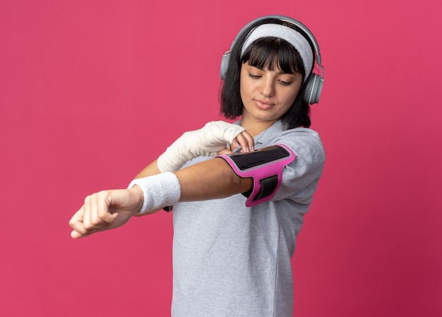 Giovane ragazza fitness che indossa fascia con mano fasciata e fascia da braccio per smartphone che sembra sicura in piedi su sfondo rosa