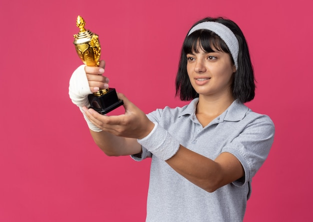 Giovane ragazza fitness che indossa la fascia con la mano bendata che tiene il trofeo guardandolo felice e felice sorridente pleased
