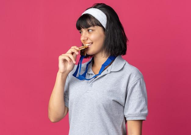 Giovane ragazza fitness che indossa fascia con medaglia d'oro intorno al collo mordendola come un campione in piedi su sfondo rosa
