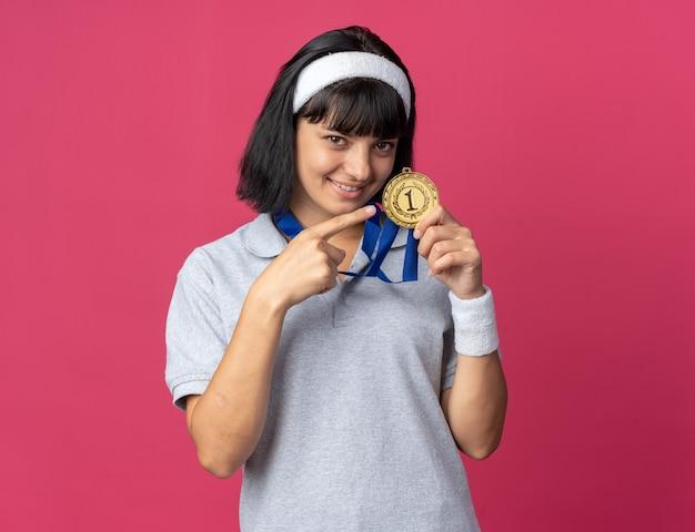 Giovane ragazza fitness che indossa fascia con medaglia d'oro intorno al collo che punta con il dito indice sorridendo allegramente in piedi su sfondo rosa