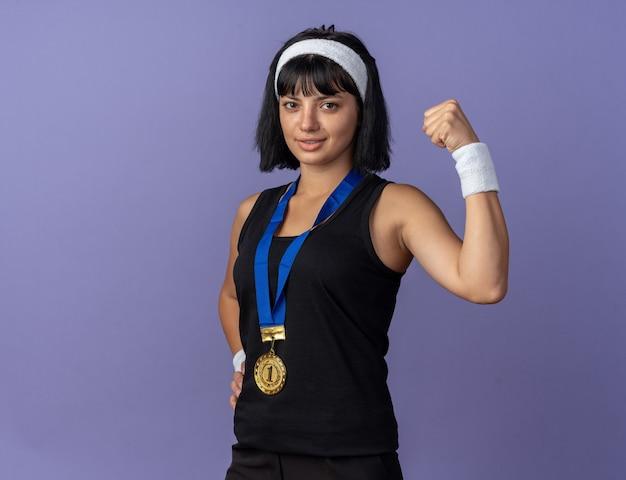 목에 금메달이 달린 머리띠를 한 젊은 피트니스 소녀는 파란색 배경 위에 자신감을 보이며 주먹을 들고 있다