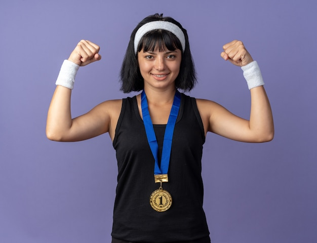 首の周りに金メダルとヘッドバンドを身に着けている若いフィットネスの女の子は、青い背景の上に立っている勝者のように幸せで自信を持ってポーズをとって拳を上げます