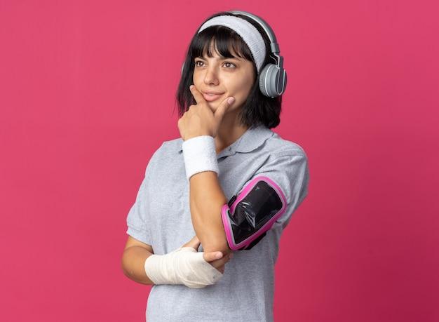 顔に物思いにふける表情で脇を見てスマートフォン用のヘッドホンとアームバンドとヘッドバンドを身に着けている若いフィットネスの女の子