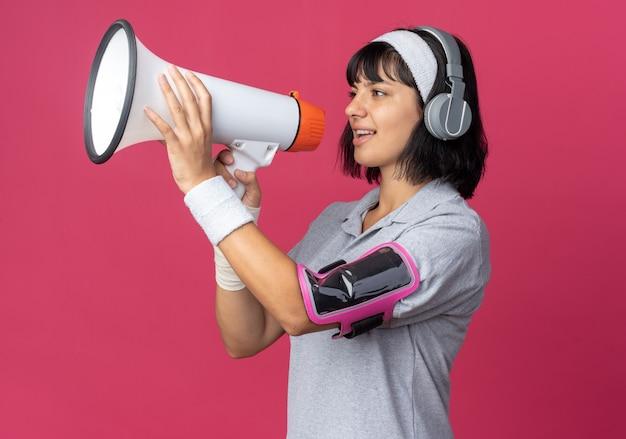 헤드폰과 완장으로 머리띠를 하고 있는 젊은 피트니스 소녀는 분홍색 배경 위에 서 있는 메가폰에 행복하고 자신감 있게 소리를 지르고 있습니다.