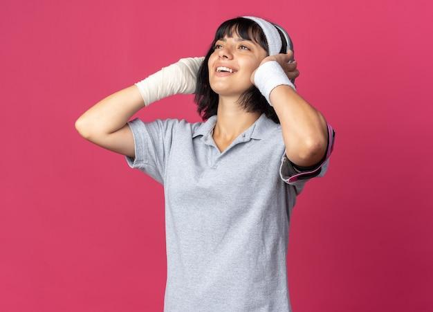 헤드폰을 끼고 머리띠를 하고 붕대를 감은 손으로 분홍색 배경 위에 서 있는 그녀가 좋아하는 음악을 즐기며 즐겁게 웃고 있는 젊은 피트니스 소녀