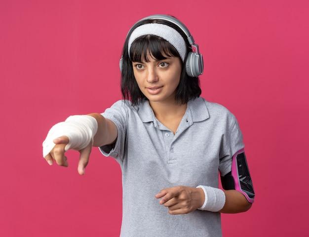 Giovane ragazza fitness che indossa fascia con cuffie e fascia da braccio per smartphone che guarda da parte puntando con il dito indice a qualcosa in piedi su sfondo rosa