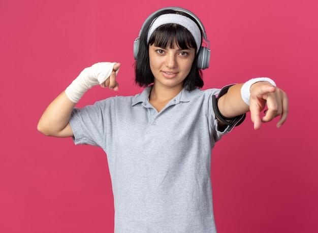 자신감이 웃는 카메라에 검지 손가락으로 가리키는 헤드폰으로 머리띠를 착용하는 젊은 피트니스 소녀