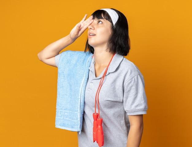 머리띠를 하고 목에 줄넘기를 하고 어깨에 수건을 두른 젊은 피트니스 소녀는 오렌지색 배경 위에 서서 이마에 손을 대고 지겹고 지루해 보인다