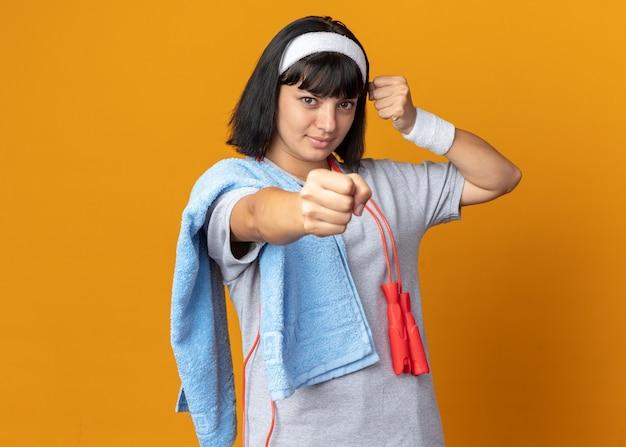 머리띠를 하고 목에 밧줄을 묶고 어깨에 수건을 두른 젊은 피트니스 소녀는 주황색 배경 위에 자신감 있게 서 있는 카메라를 향해 주먹을 쥔 모습