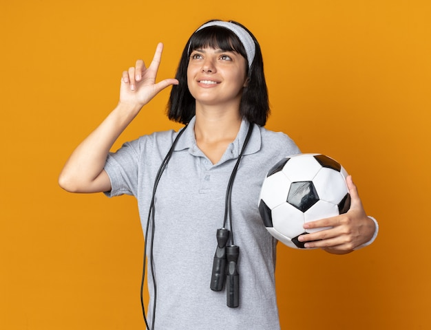 首の周りに縄跳びとヘッドバンドを身に着けている若いフィットネスの女の子は、人差し指を見せて笑顔を見上げてサッカーボールを保持しています