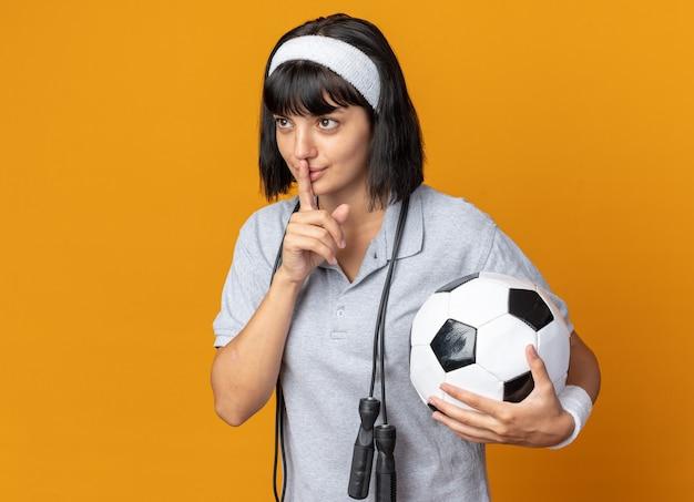 주황색 배경 위에 서 있는 입술에 손가락으로 침묵 제스처를 만드는 축구공을 들고 목에 밧줄을 건너뛰는 머리띠를 한 젊은 피트니스 소녀